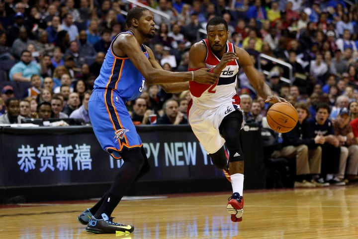 Feb 1, 2014; Washington, DC, USA; Washington Wizards point guard John Wall (2) dribbles the ball as Oklahoma City Thunder small forward Kevin Durant (35) defends in the first quarter at Verizon Center. Mandatory Credit: Geoff Burke-USA TODAY Sports