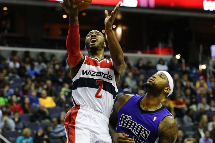 John Wall drives past Demarcus Cousins